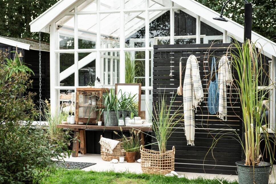 Glashaus mit Sprossenfenstern und schwarzem Holzsichtschutz mit Außendusche