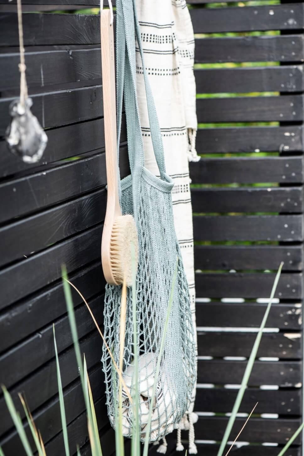 Handtuch und Holzbürste hängen an schwarzem Holzsichtschutz einer Außendusche