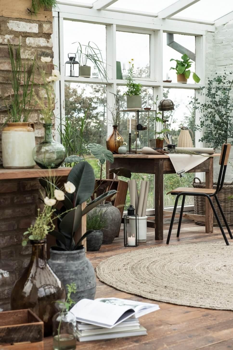 Gemütlich mit Holzmöbeln und vielen Zimmerpflanzen eingerichtetes Zimmer in skandinavischem Ferienhaus