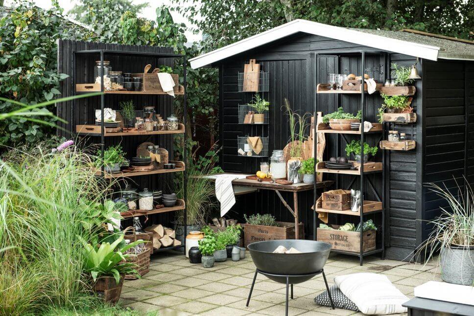 Rustikale Outdoorküche Rustikale Outdoorküche mit Holztisch, Metallregalen und vielen Kübelpflanzen