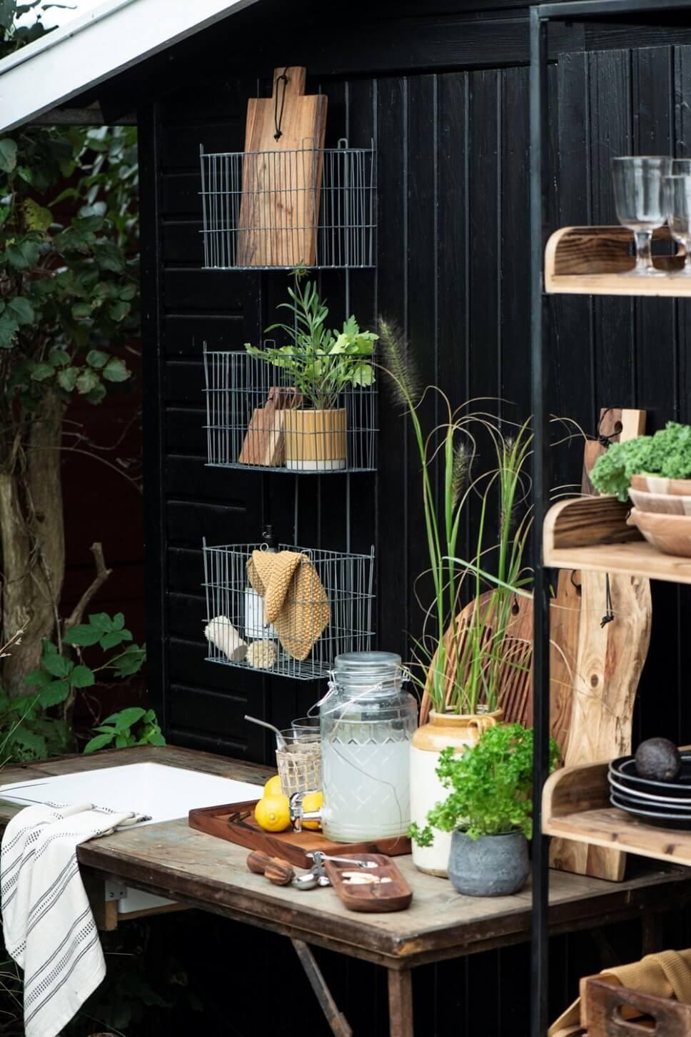 Rustikale Outdoorküche mit Holztisch, Metallregalen und vielen Kübelpflanzen