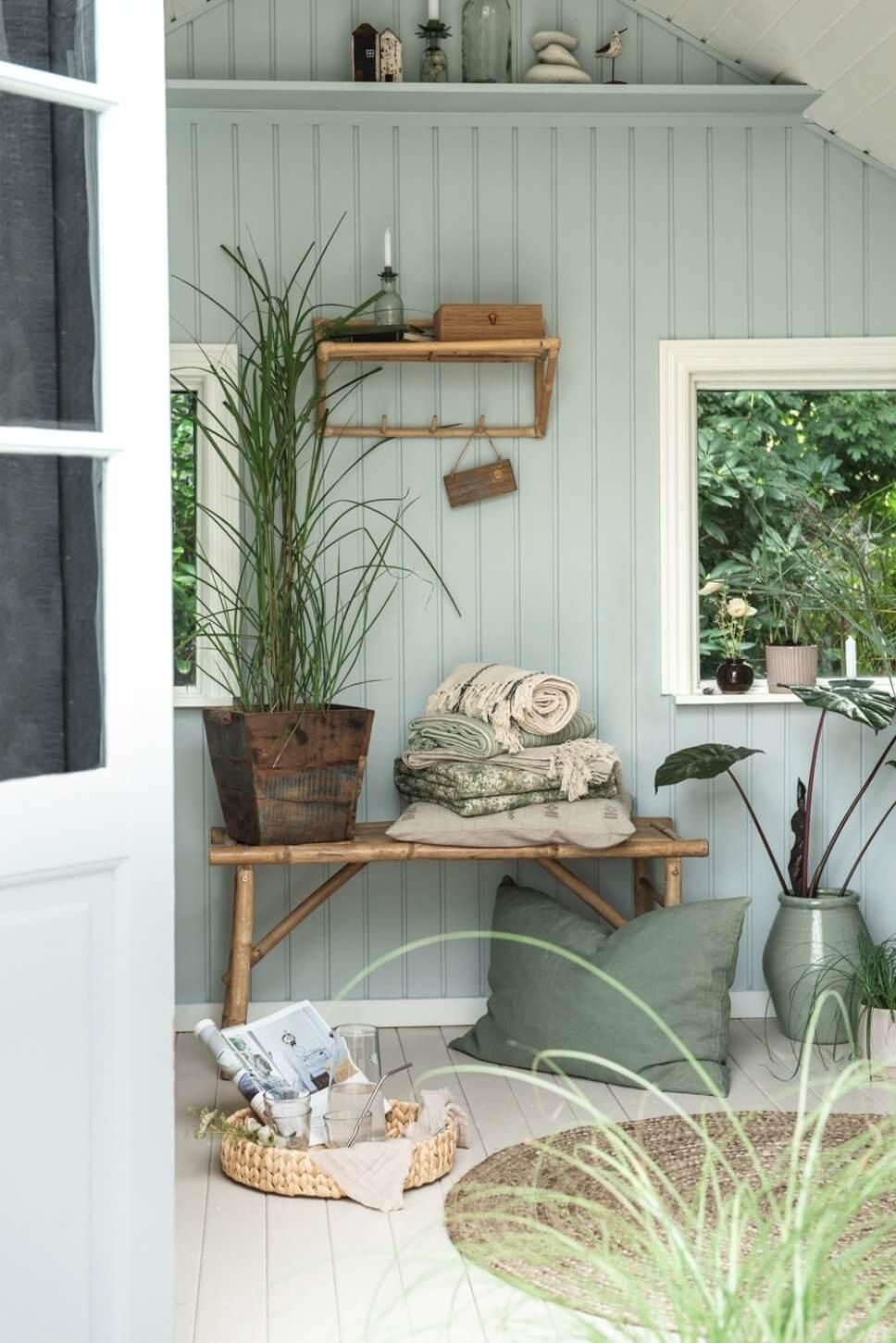 Zimmer mit hellblauer Holzvertäfelung in skandinavischem Ferienhaus