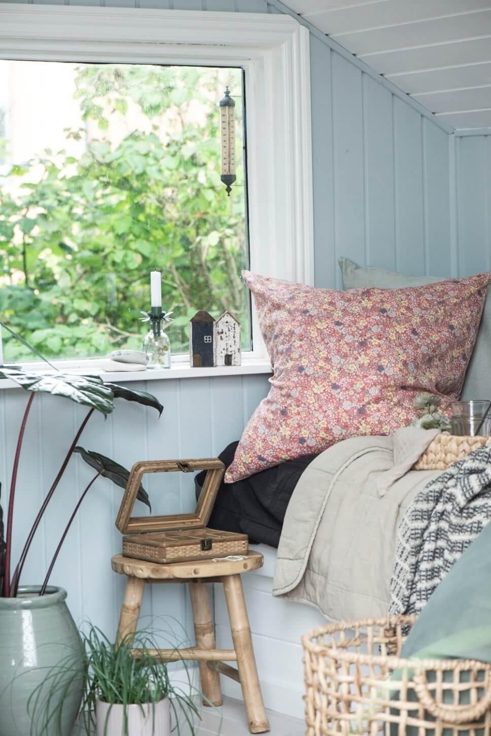Gemütlich eingerichtetes Schlafzimmer mit hellblauer Holzvertäfelung in skandinavischem Ferienhaus