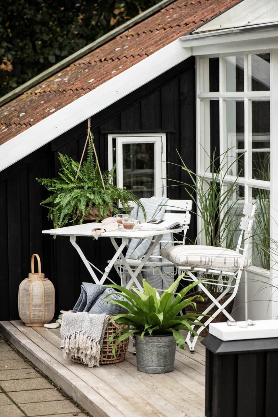 Gemütlich mit Bistromöbeln und vielen Kübelflanzen eingerichtete Terrasse in Skandinavien