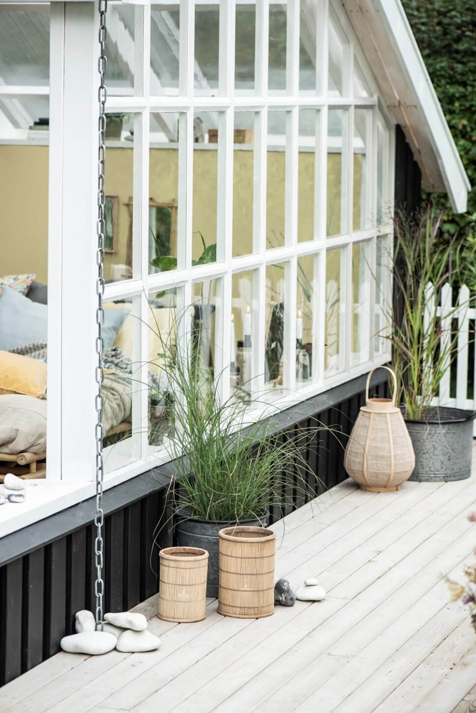Blick durch Sprossenfenster in gemütlich eingerichtetes Schlafzimmer in skandinavischem Ferienhaus
