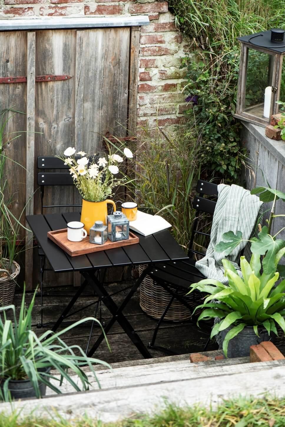 Gemütlich mit Bistromöbeln und vielen Kübelpflanzen eingerichtete Terrasse in Skandinavien