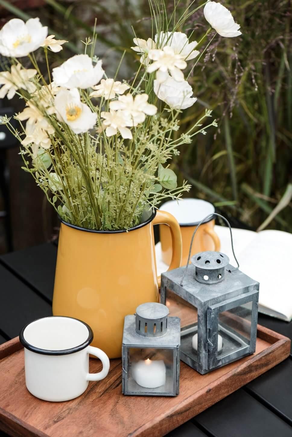 Blumen im Emaille-Krug, Zink-Laternen und Becher auf Holztablett