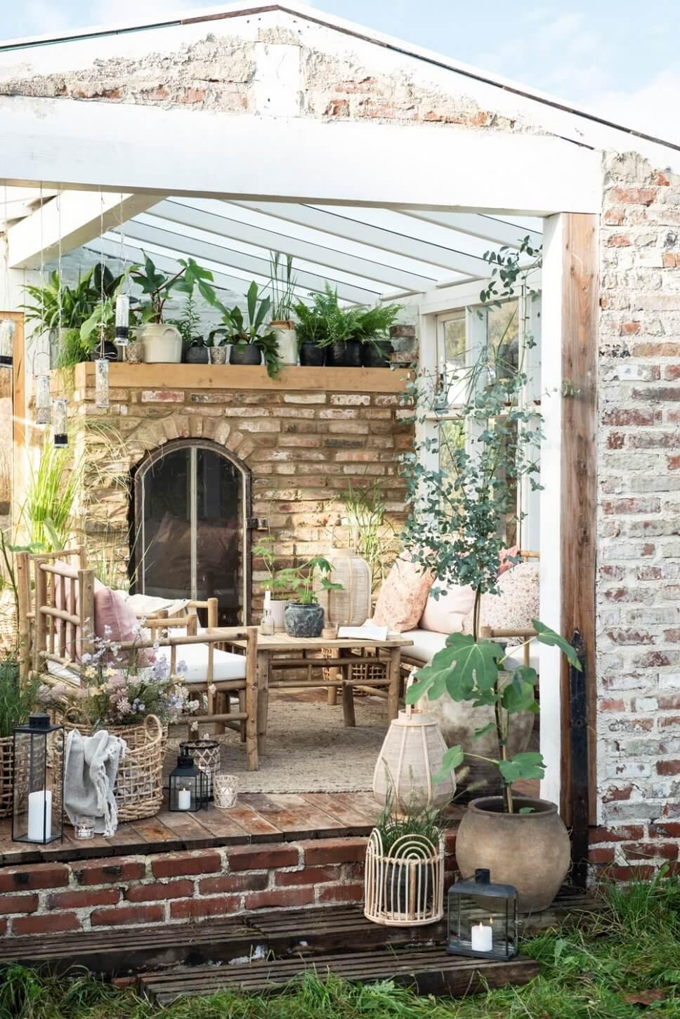 Gemütlich mit Bambusmöbeln und vielen Zimmerpflanzen eingerichtetes Gartenzimmer in Skandinavien
