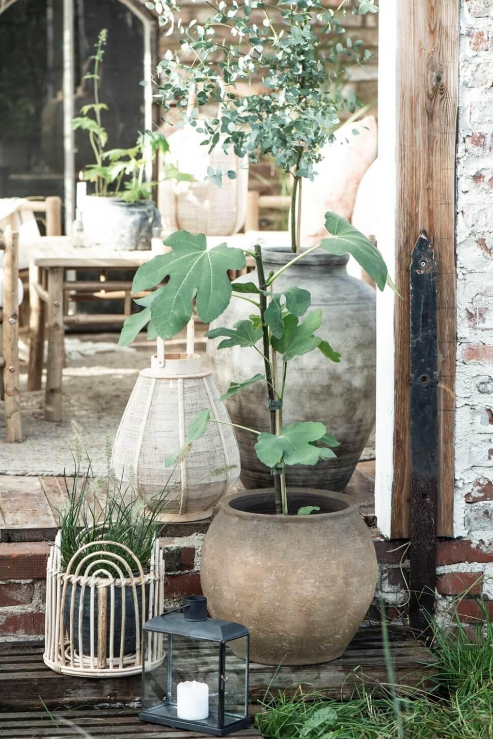 Kübelpflanzen und Laternen am Rand einer gemütlich eingerichtete Terrasse in Skandinavien