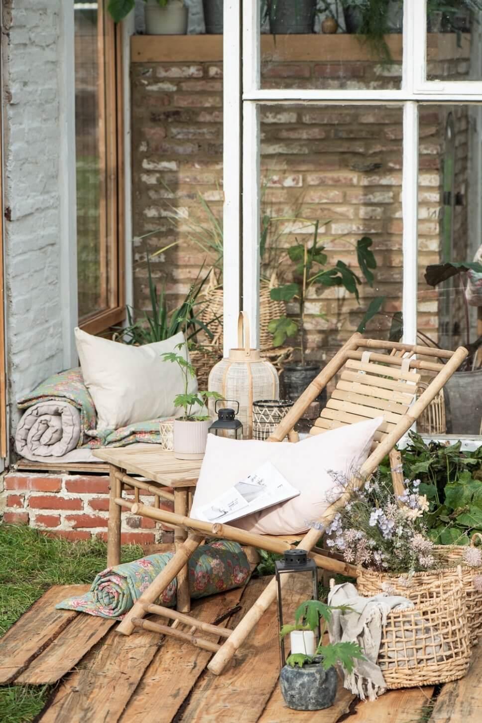 Gemütlich mit Bambusmöbeln und vielen Kübelpflanzen eingerichtete Terrasse in Skandinavien