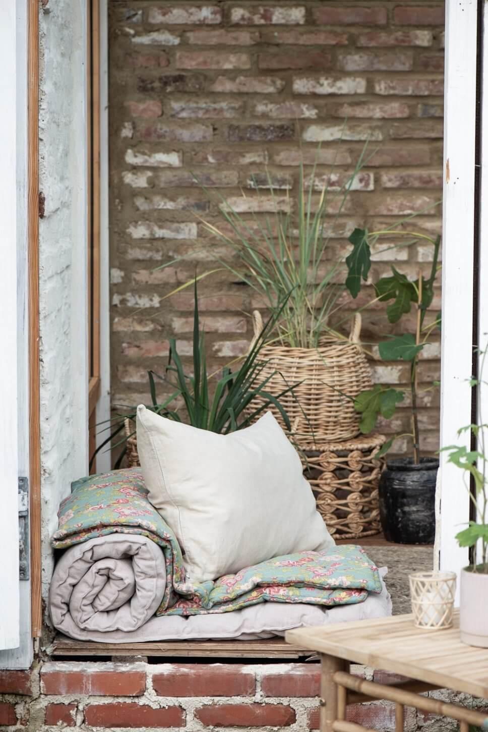 Rollmatratzen, Plaids und Kissen liegen in einem geöffneten Fenster im Backsteingebäude