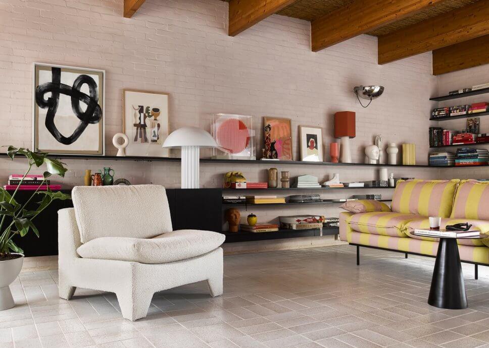 Mit Boucléstoff bezogener Sessel und gestreiftes Sofa in modernem Wohnzimmer