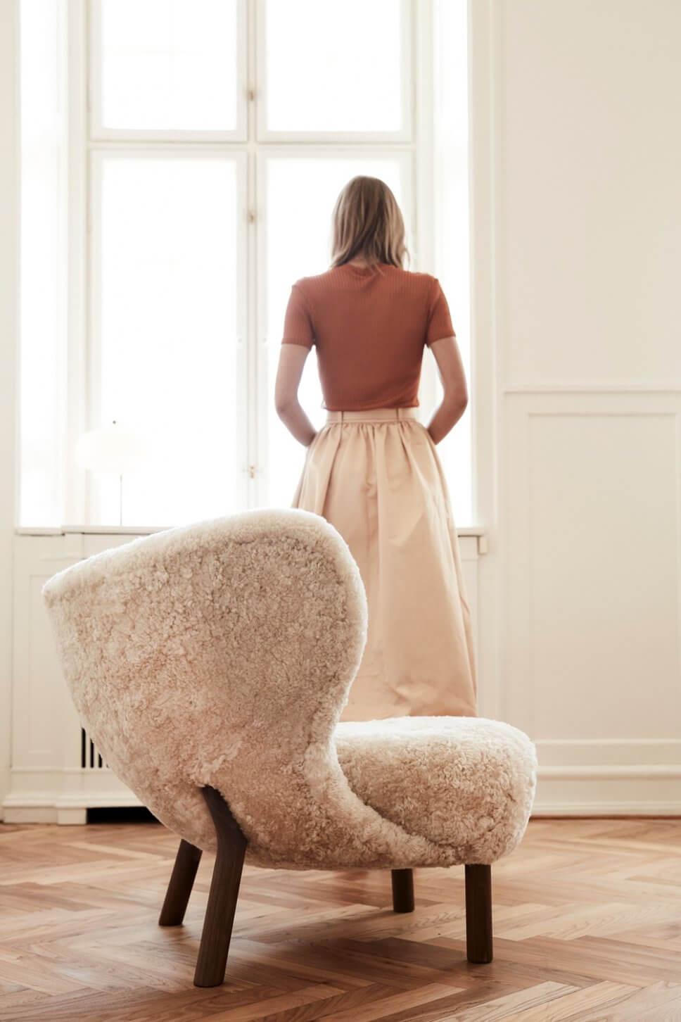 Junge Frau steht neben einem mit Schaffell bezogenen Sessel