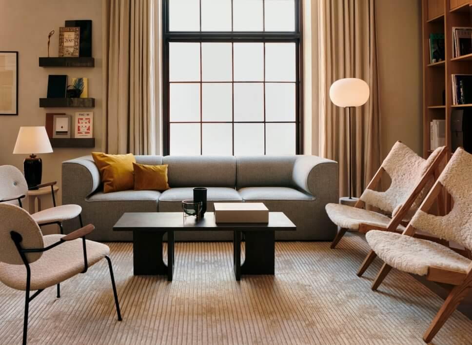 Modernes Wohnzimmer mit schlichtem Sofa und drei mit Schaffell bezogenem Sesseln