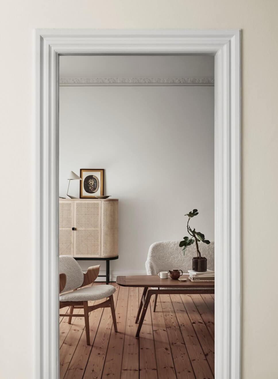 Modernes Wohnzimmer mit Schaffell bezogenen Sofas und Ohrensessel