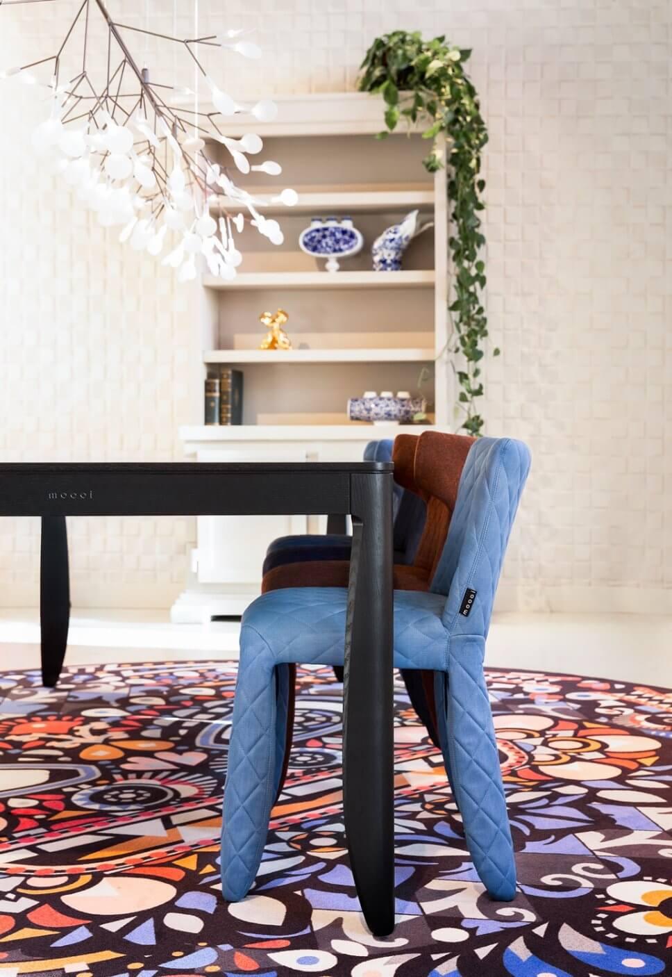 Voll gepolsterte Stühle stehen an einem Esstisch