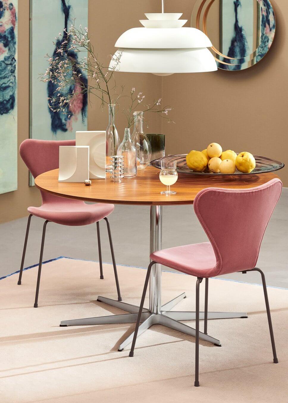 Zwei gepolsterte Stühle stehen an einem runden Esstisch