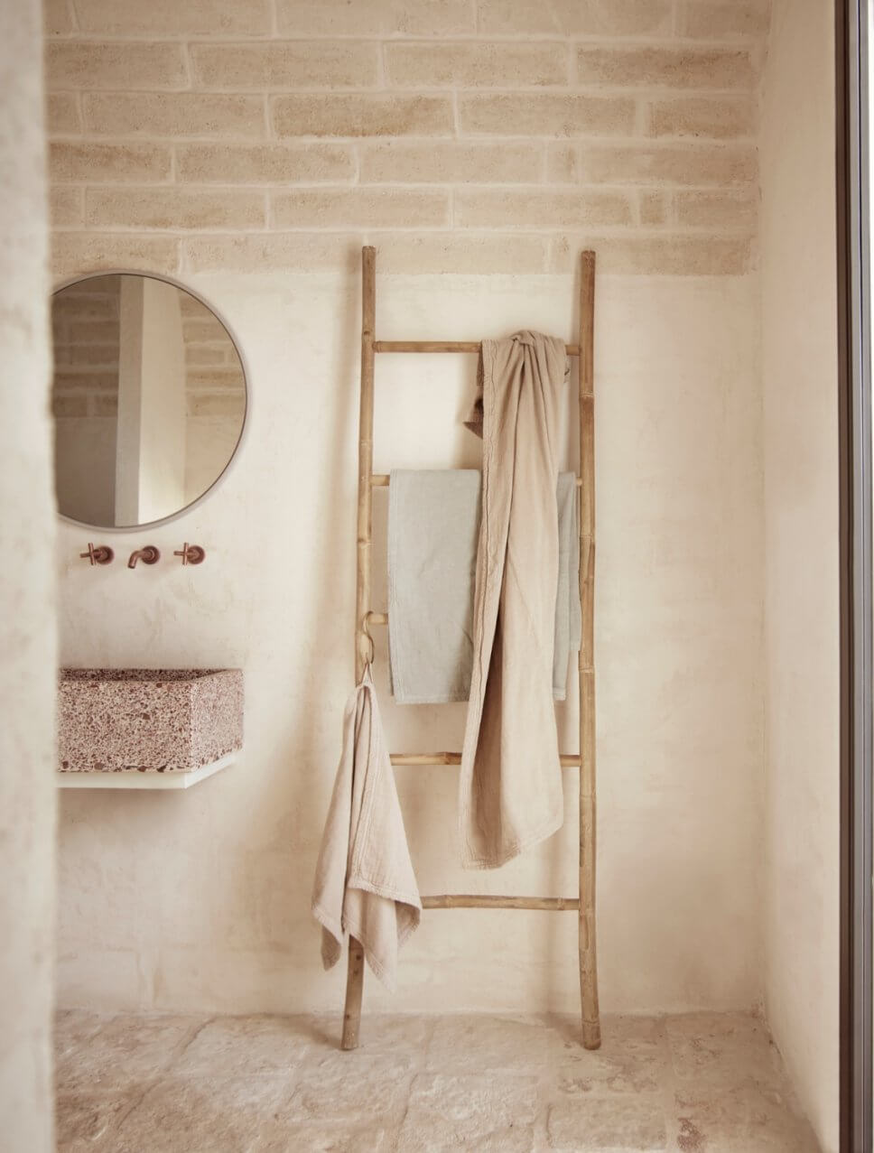 Badezimmer mit Handtuchleiter aus Bambus und Waschbecken in mediterranem Haus mit steinerner Gewölbedecke