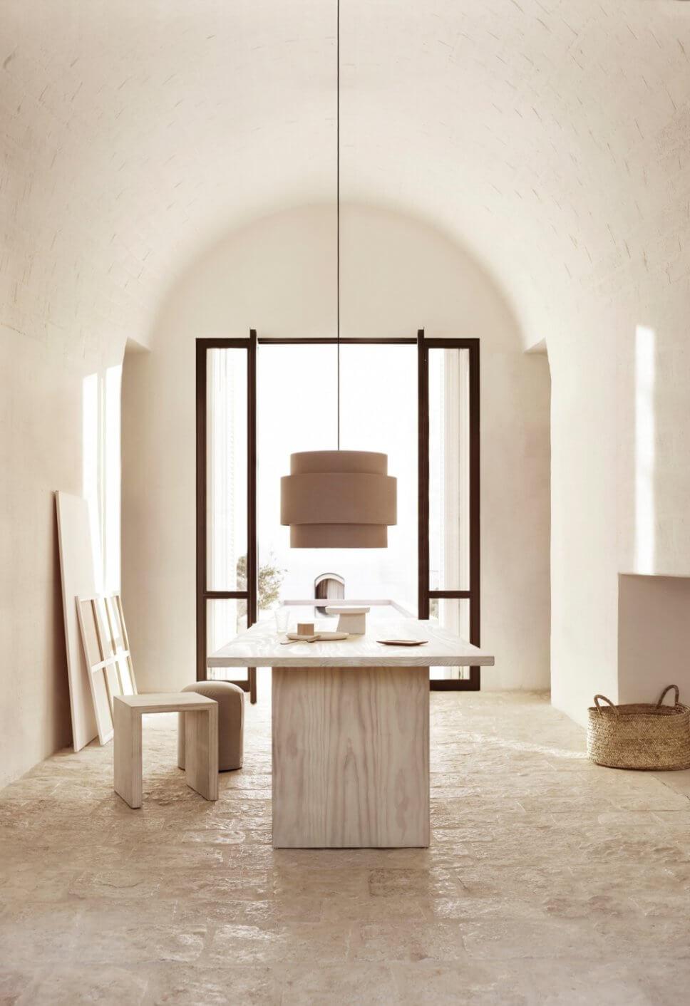 Modernes Esszimmer mit Tisch, Hockern und Hängelampe in mediterranem Haus mit steinerner Gewölbedecke