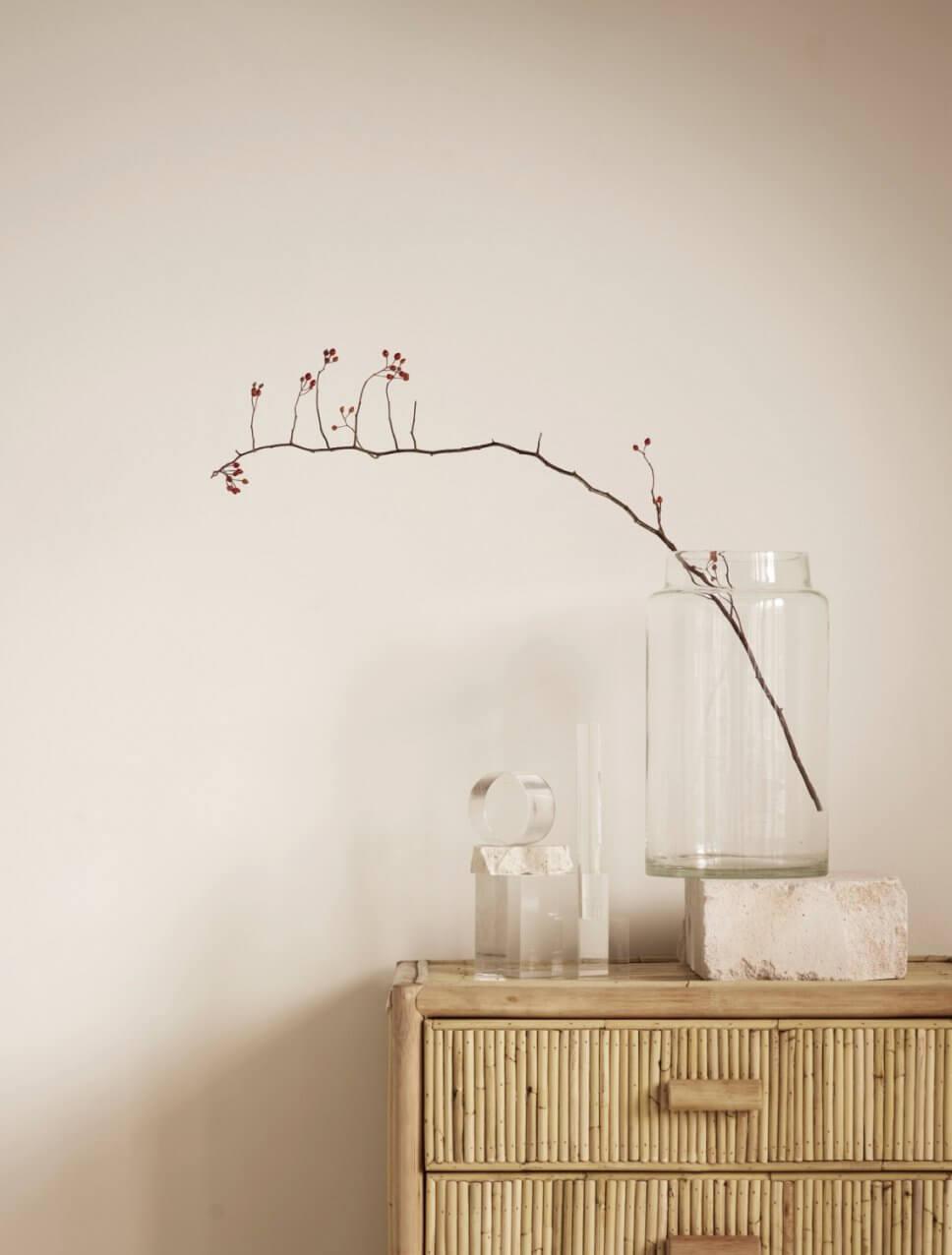 Zweig in einem großen Glas steht auf Bambus-Kommode