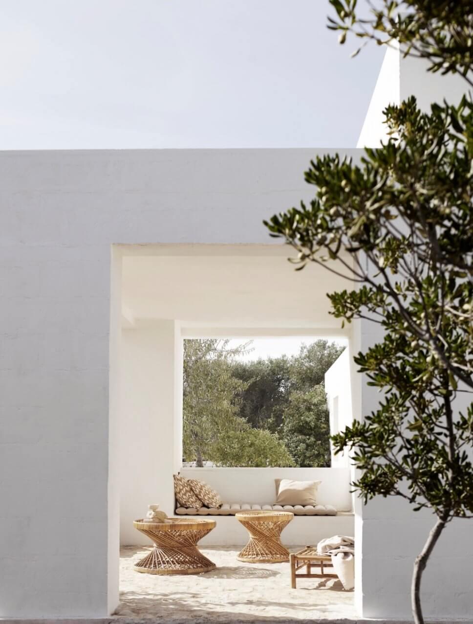 Mediterranes, weißes Haus mit Rattan-Tischen auf der Terrasse