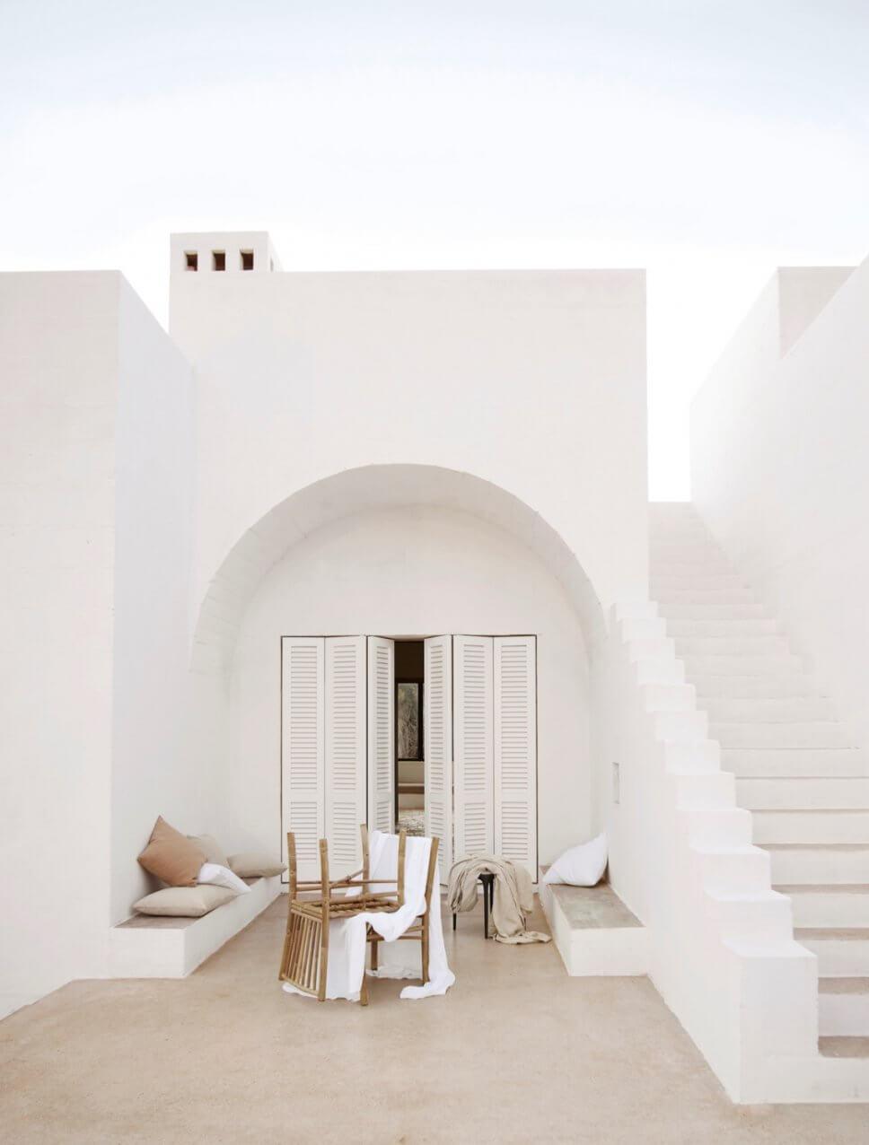 Mediterranes, weißes Haus mit Bambus-Gartenmöbeln auf der Terrasse