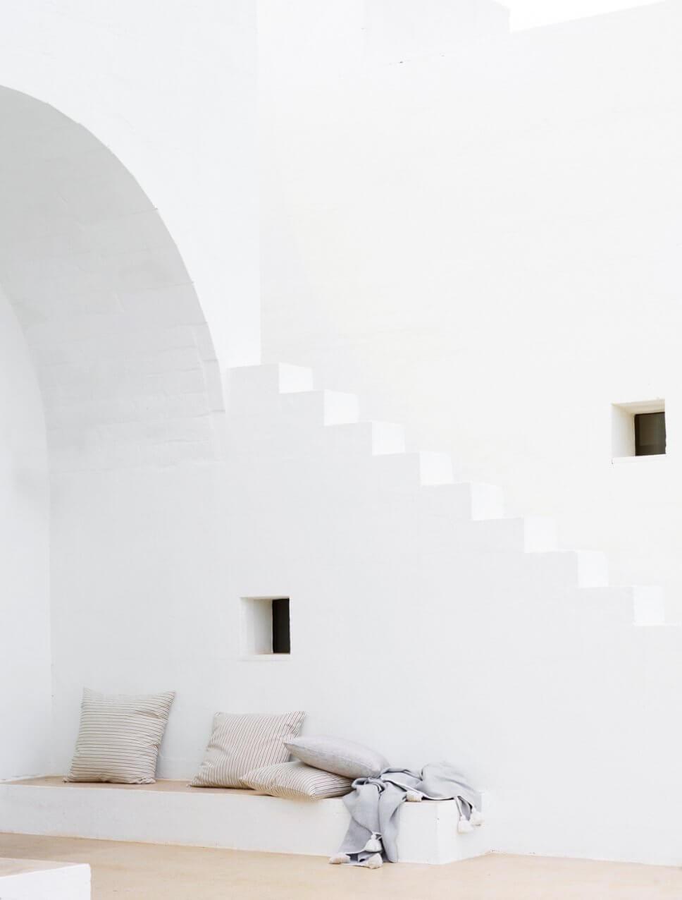 Mediterranes, weißes Haus mit Kissen auf einer Sitzbank