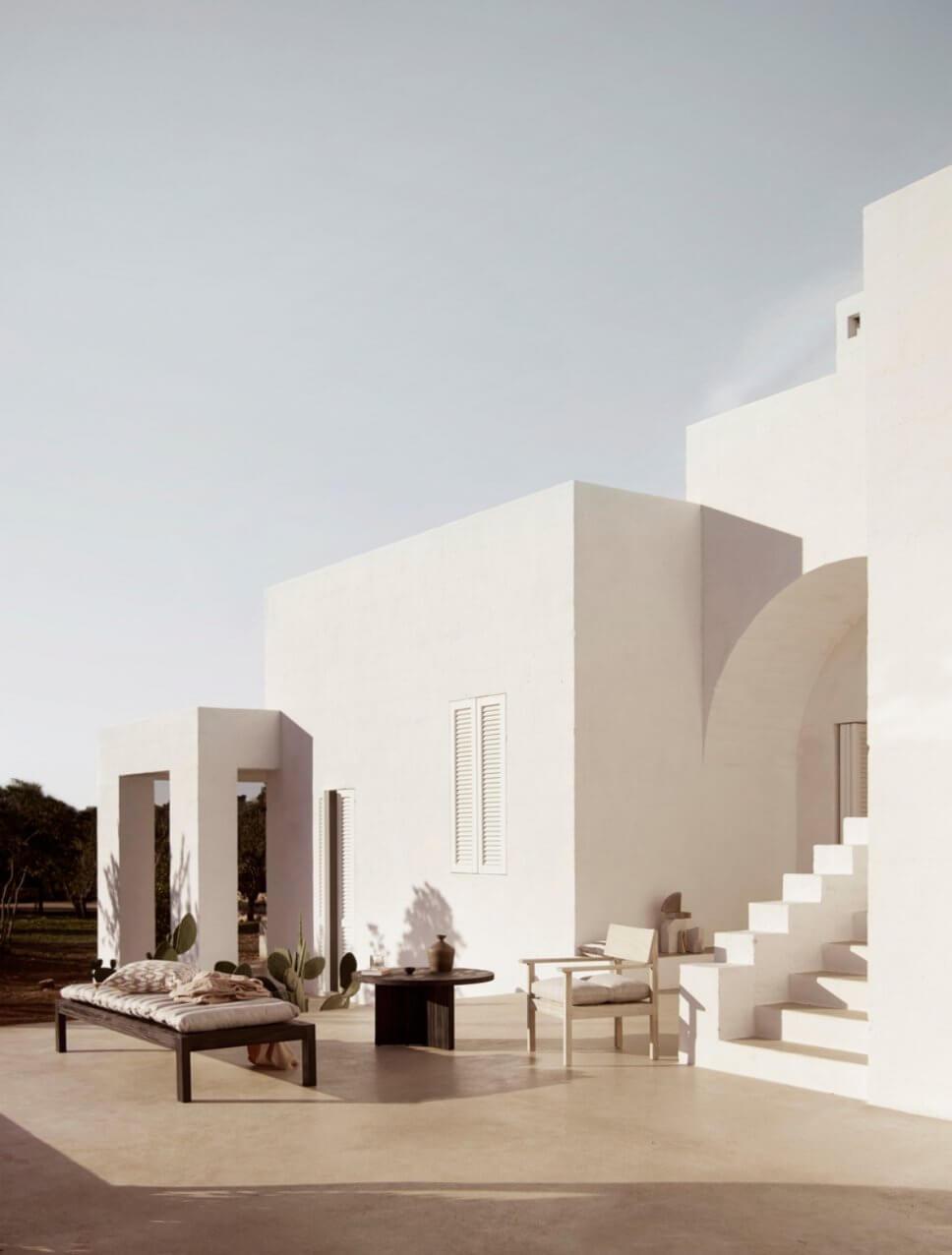 Mediterranes, weißes Haus mit Holz-Gartenmöbeln auf der Terrasse