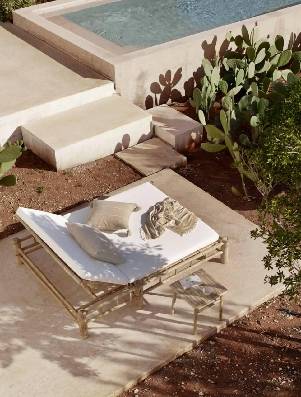 Bambus-Gartenliegen auf der Terrasse neben einem Pool