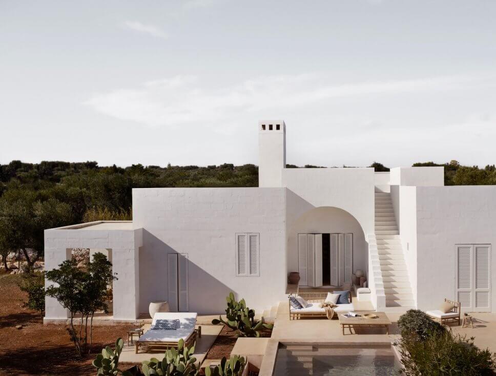 Mediterranes, weißes Haus mit Bambus-Gartenmöbeln auf den Terrassen
