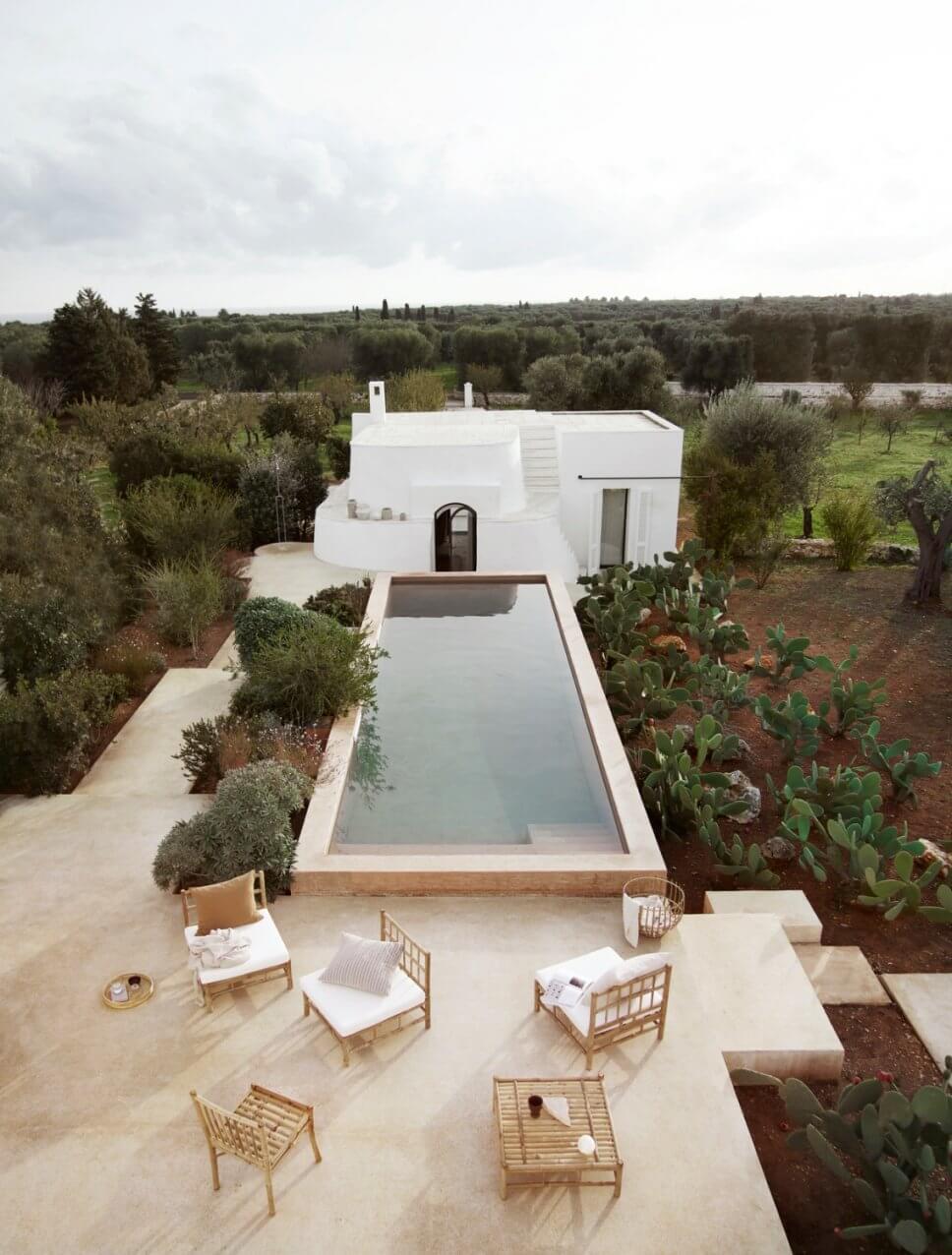 Mediterranes, weißes Haus mit Pool und Bambus-Gartenmöbeln auf den Terrassen