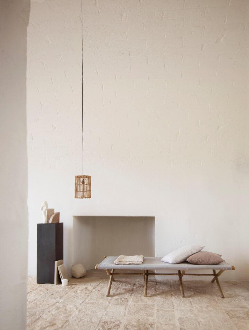 Minimalistisches Wohnzimmer mit Hängelampe und Klapp-Feldbett aus Bambus in mediterranem Haus mit Steinboden