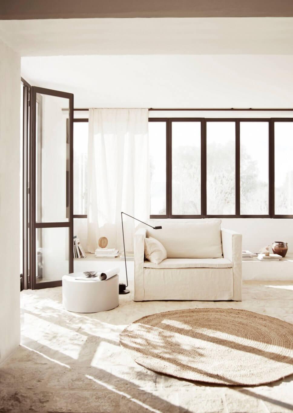 Modernes Wohnzimmer mit weißem Sessel in mediterranem Haus mit Steinboden