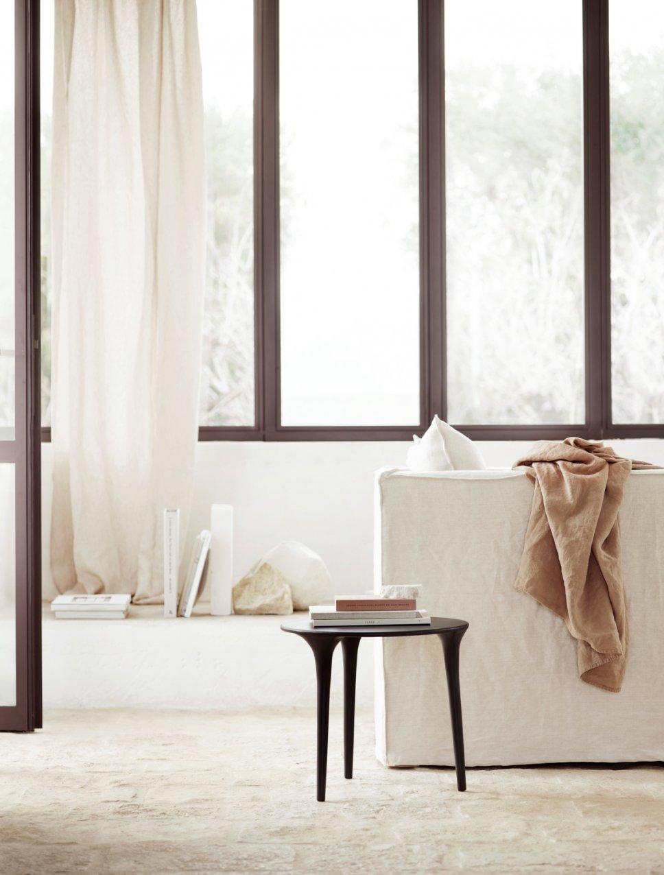 Modernes Wohnzimmer mit weißem Sessel und schwarzem Beistelltisch in mediterranem Haus mit Steinboden