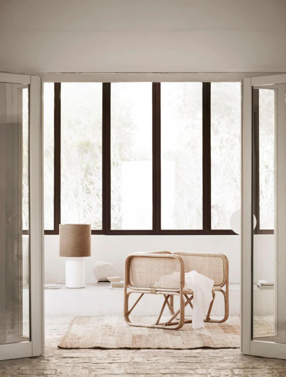 Modernes Wohnzimmer mit Rattan-Sessel in mediterranem Haus mit Steinboden