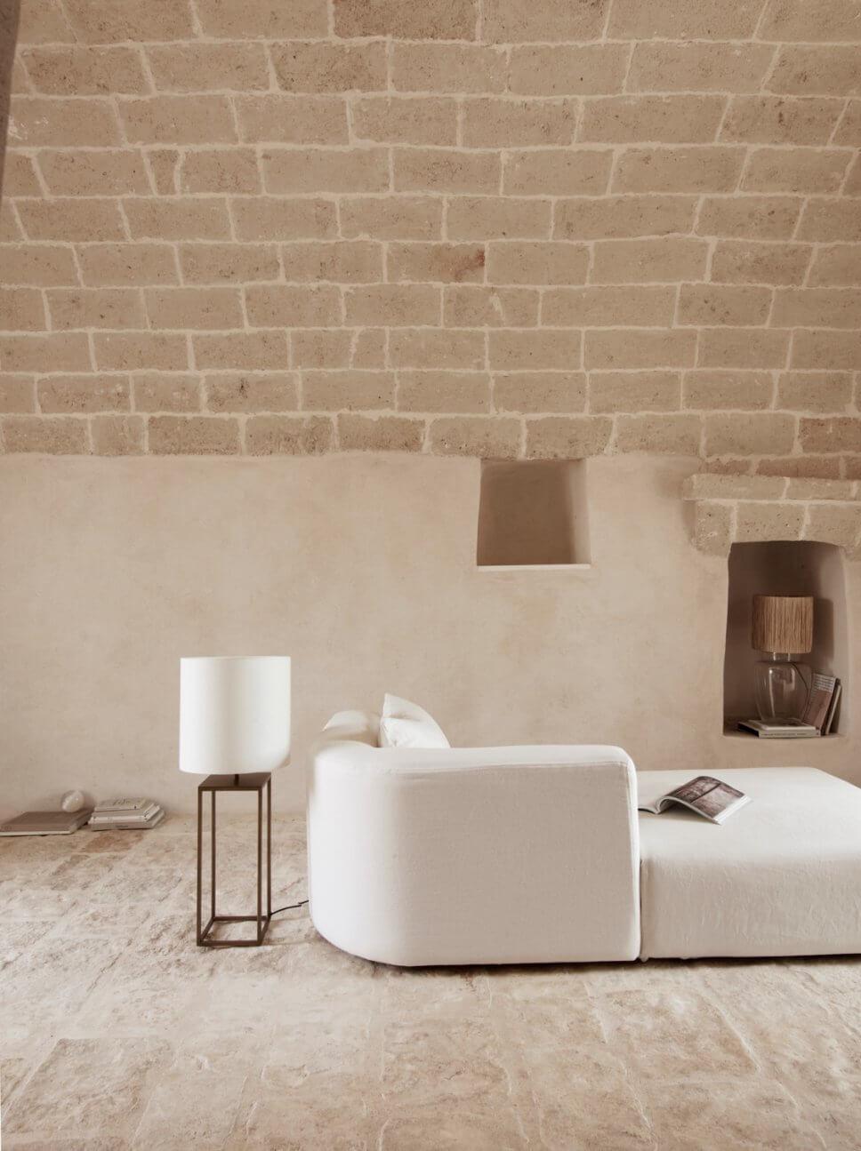 Modernes Wohnzimmer mit weißem Sofa in mediterranem Haus mit steinerner Gewölbedecke