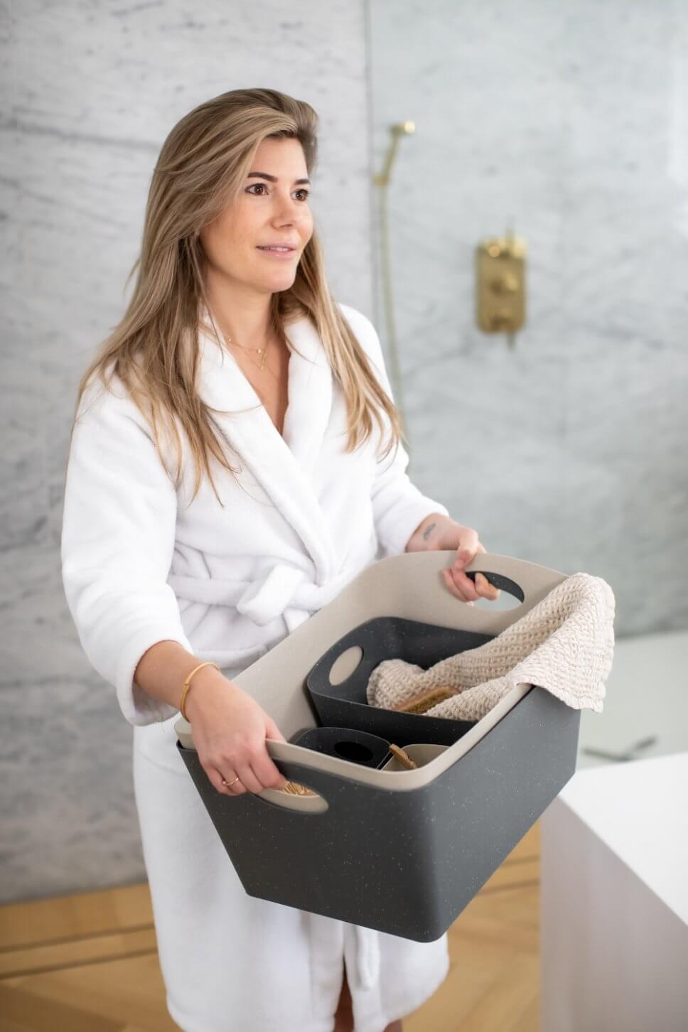 Frau im Bademantel trägt Körbe mit Handtüchern und Bürsten durch modernes Badezimmer