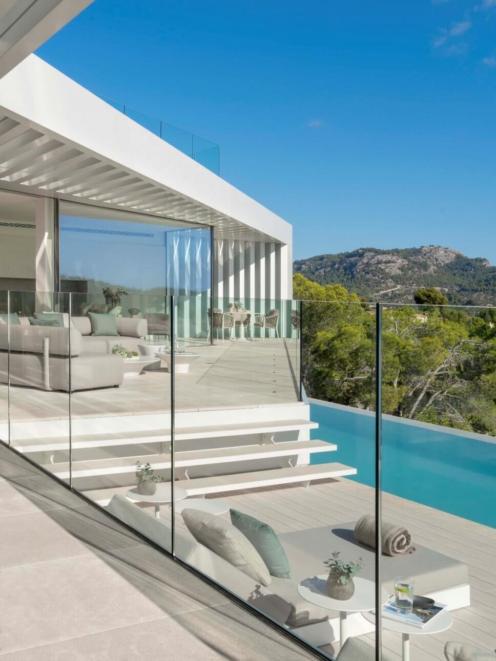 Terrasse mit zwei Sofas und zwei Liegen in moderner Villa mit Blick aufs Meer