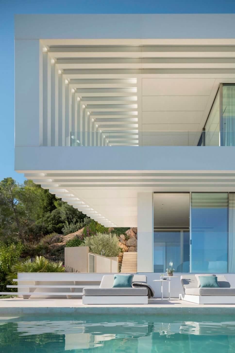 Terrasse mit zwei Liegen am Pool in moderner Villa