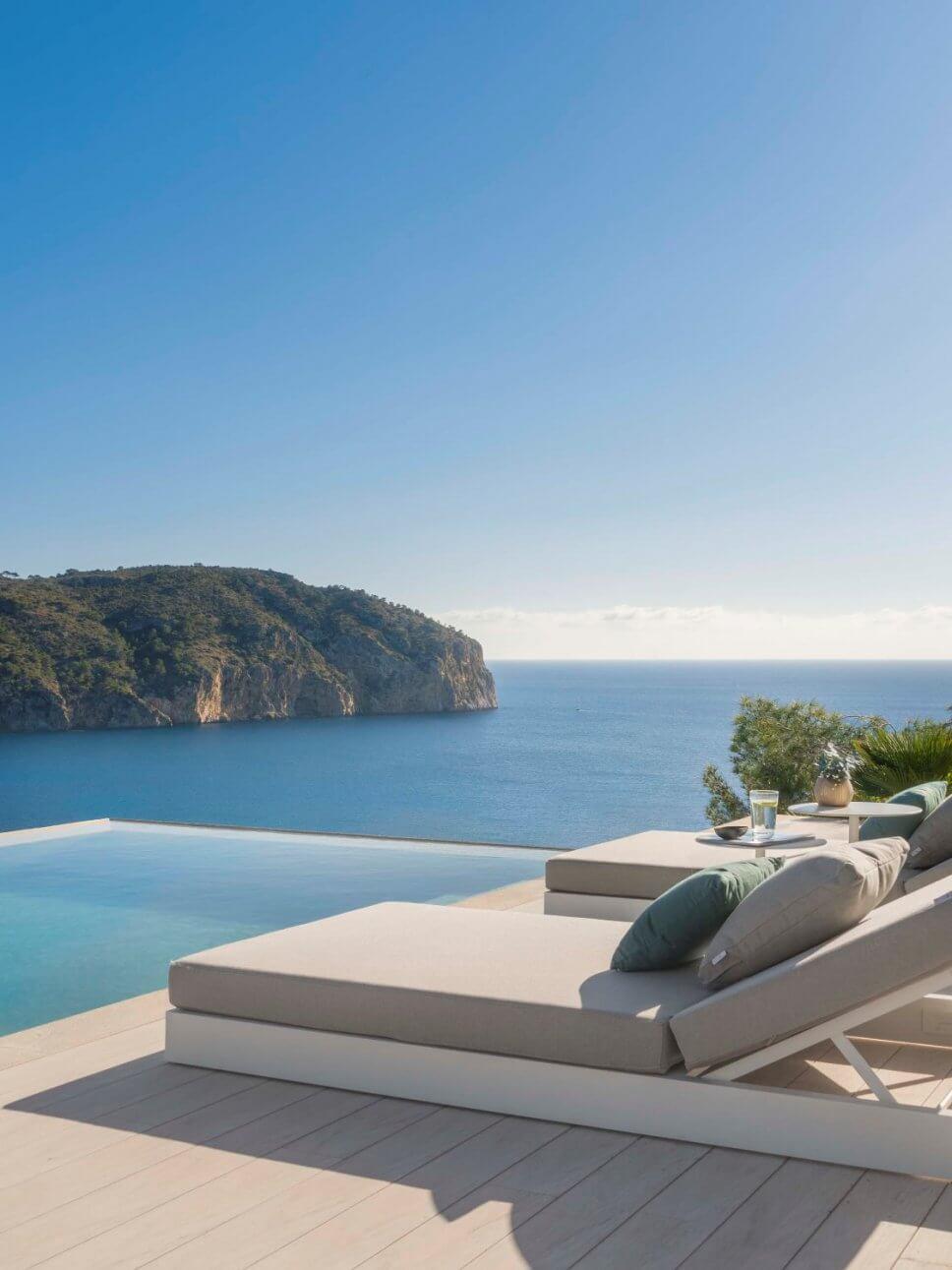 Terrasse mit zwei Liegen in moderner Villa mit Blick aufs Meer
