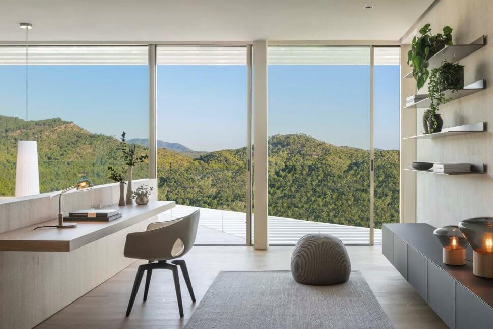 Stuhl vor Schreibplatte in moderner Villa mit Blick auf Berge