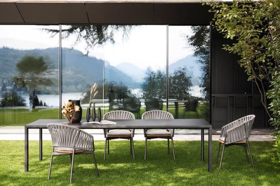 Moderne Gartenstühle stehen um einen Tisch auf Terrasse