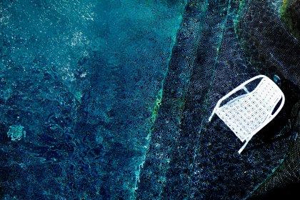 Moderner Gartenstuhl steht im Pool