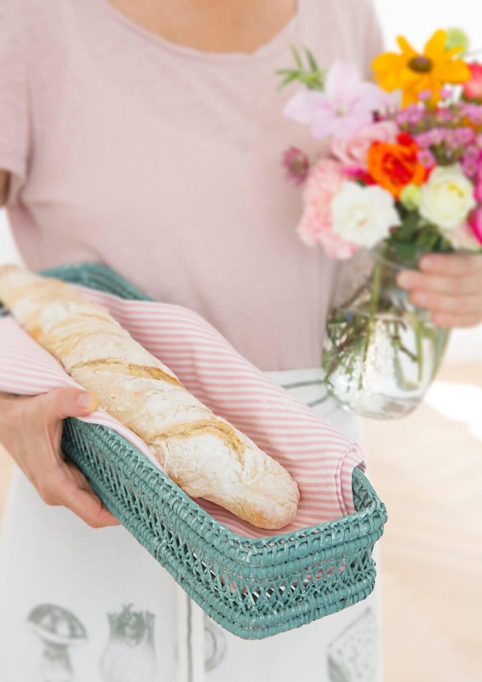 Frau trägt Blumenstrauß und Korb mit Baguette