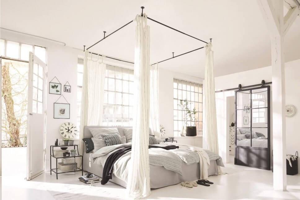 Schlafzimmer mit vielen Kissen und Decken auf dem Himmelbett