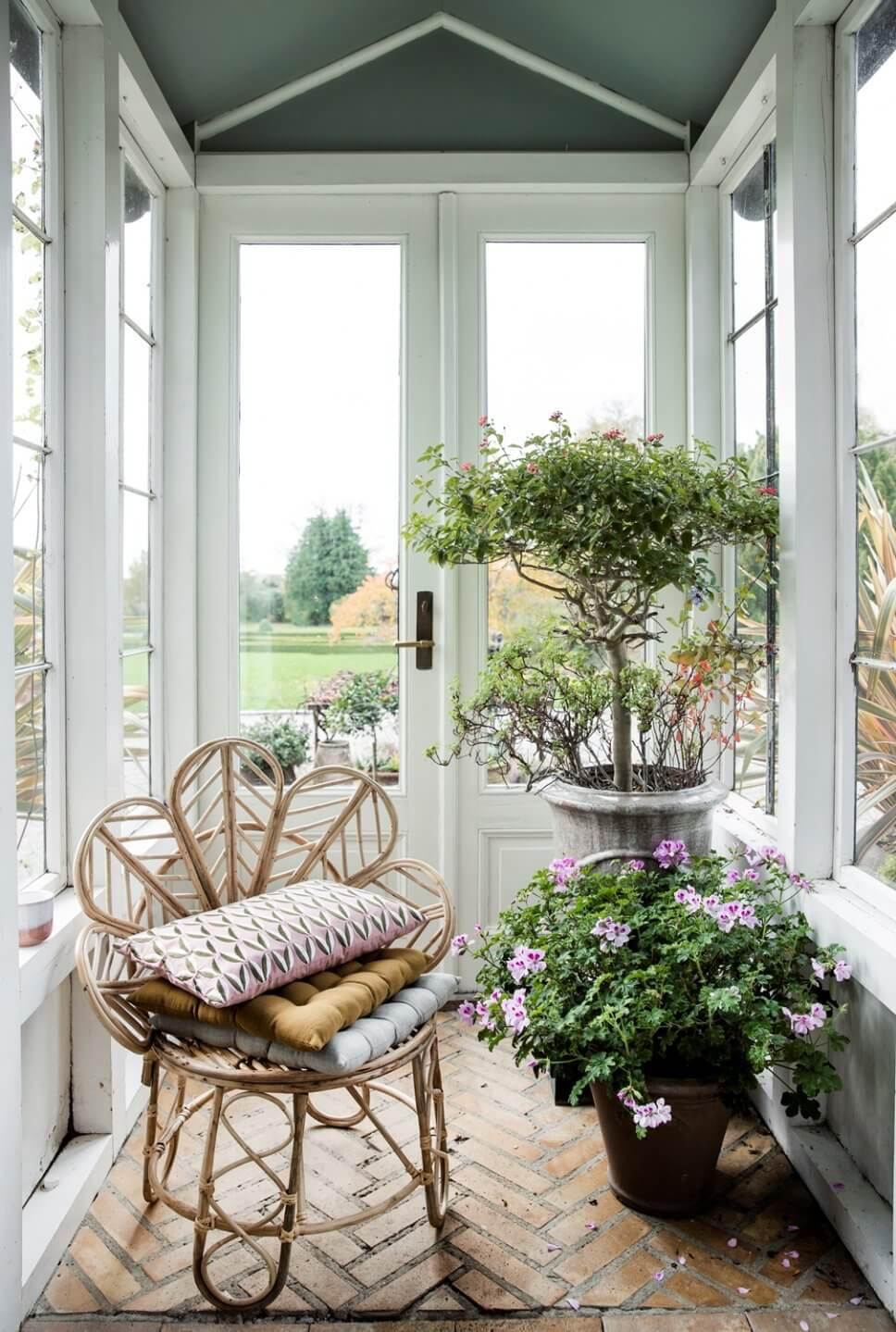 Korbsessel mit vielen Kissen vor Glastür zum Garten