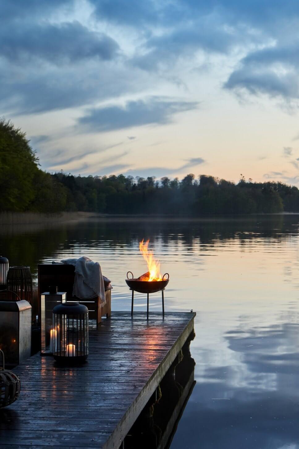 Laternen und Feuerschale auf einem Bootssteg in der Dämmerung