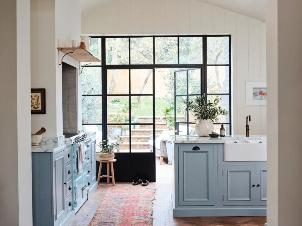 Hellblaue Landhausküche mit Glastür zum Garten