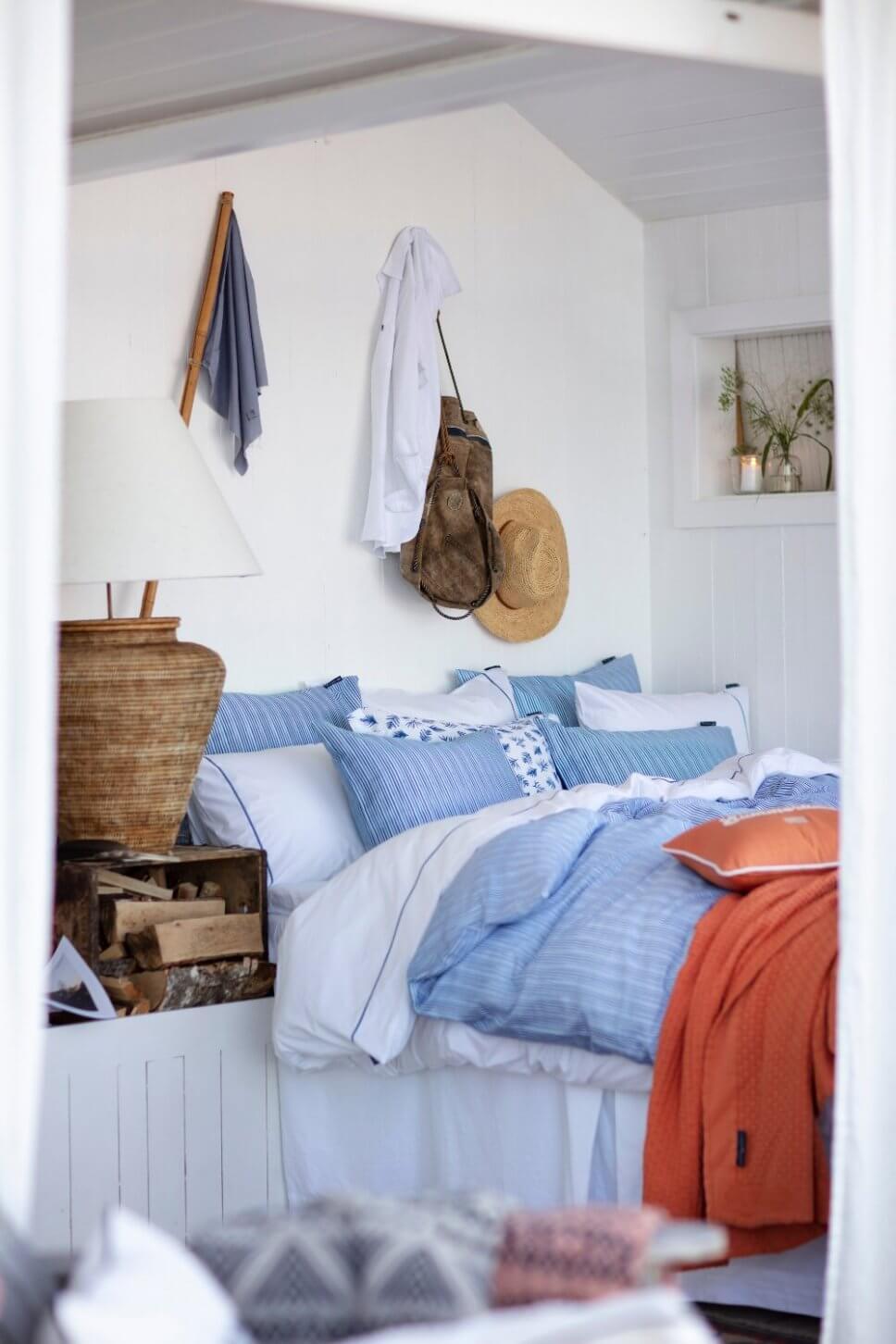 Maritimes Schlafzimmer mit blau-weißer Bettwäsche