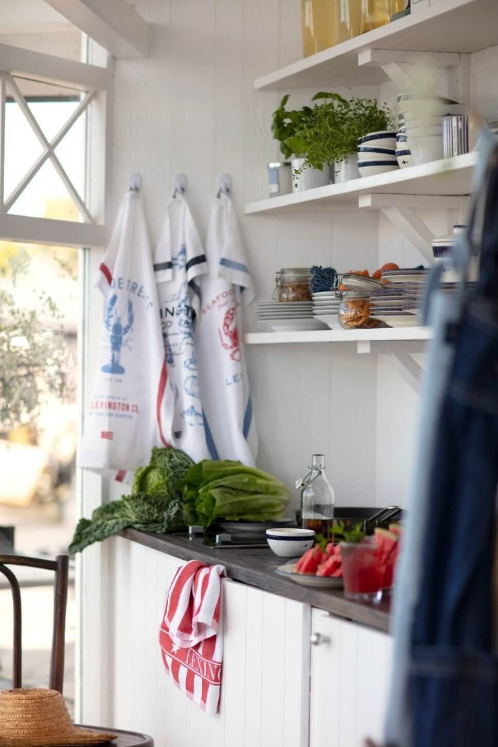 Weiß getäfelte Landhausküche mit Keramik in offenen Regalen